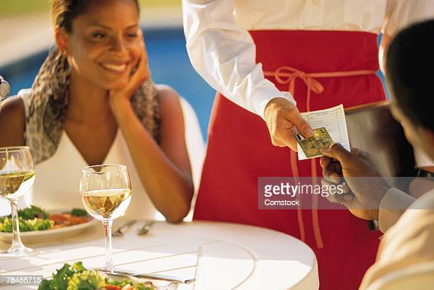 Couple at restaurant table paying for check