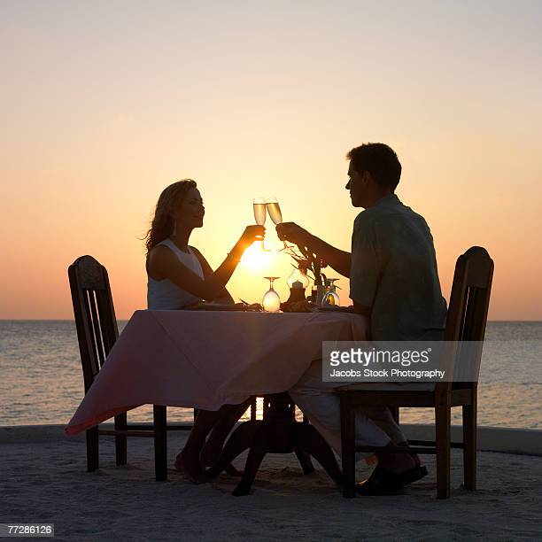 Couple at romantic dinner on beach at sunset