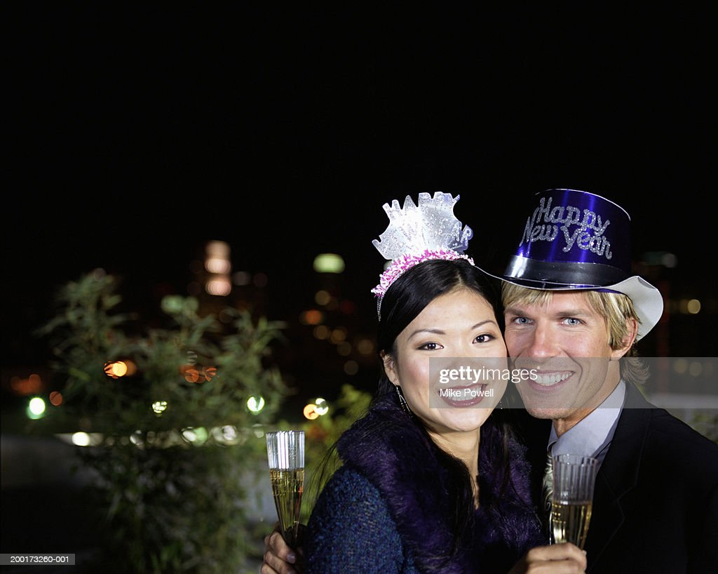 Couple at t New Years Eve party, holding champagne, portrait : Stock Photo