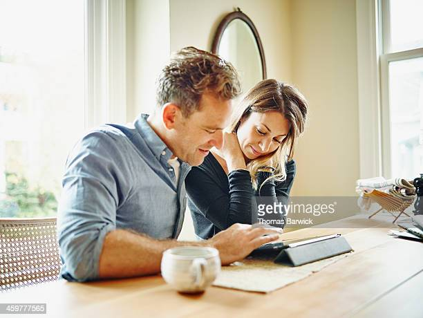 Couple at table in home working on digital tablet
