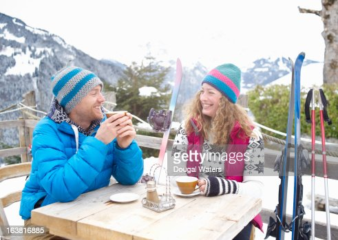 Couple at table in mountain landscape.