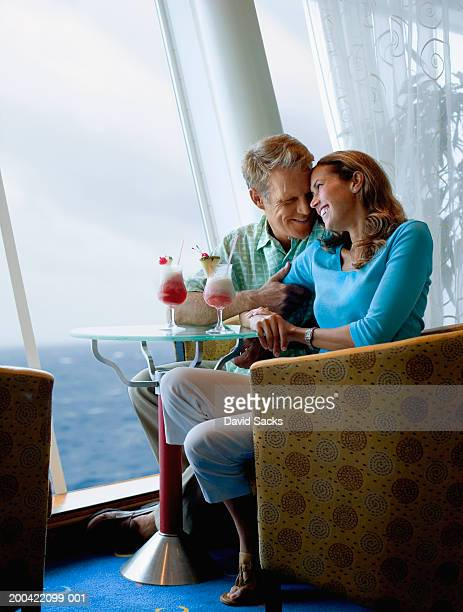 Couple at table on cruise ship near window, smiling