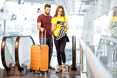 Young happy couple getting up with baggage on the escalator to the departure area of the airport during their summer vacation