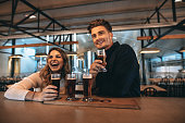 Smiling young couple at the bar with different varieties of craft beers. They are at brewery and tasting beers.