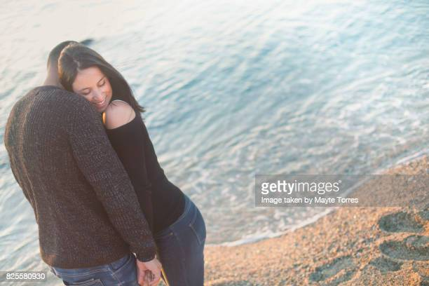 Couple at the beach standing very close