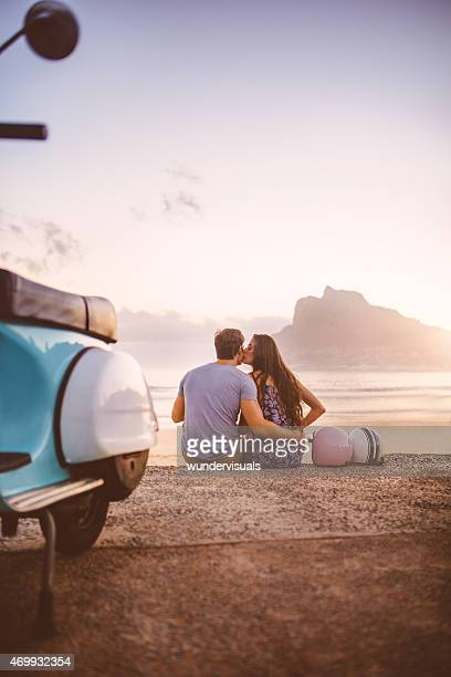 Couple at the beach with scooter on a road trip