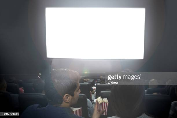 Couple at the cinema looking at a white screen