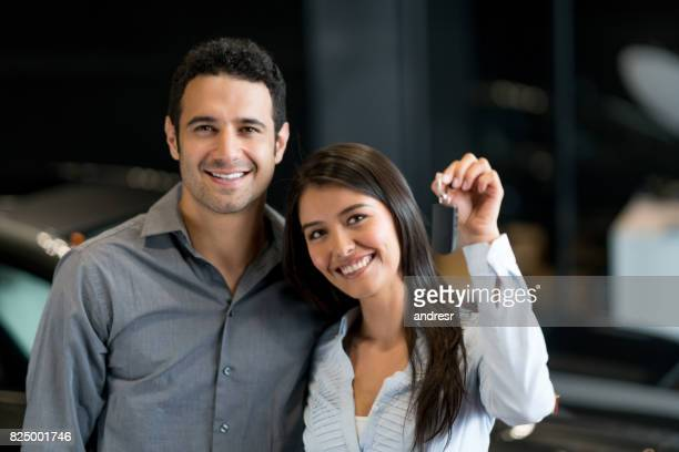 Couple at the dealership holding keys to their new car