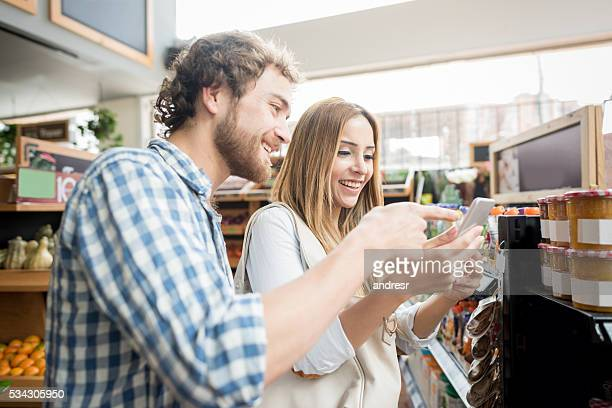 Couple at the grocery store going through a shopping list
