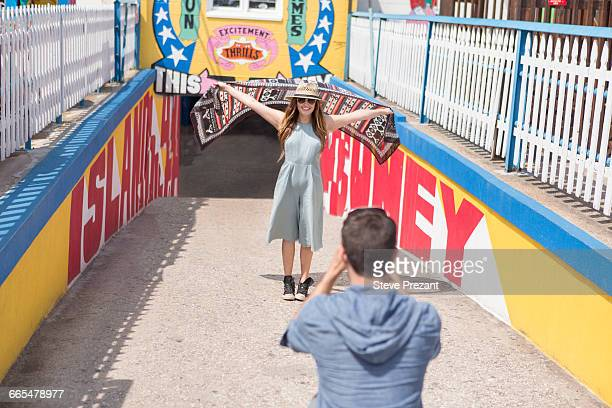Couple at tunnel entrance taking photo, Coney island, Brooklyn, New York, USA