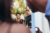 Excited couple at entrance door with wine bottle. People attending friend's housewarming party.