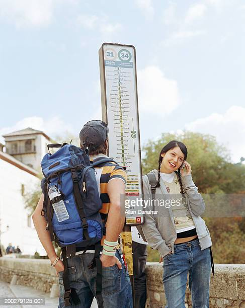 Couple backpacking standing at bus stop, woman using mobile phone