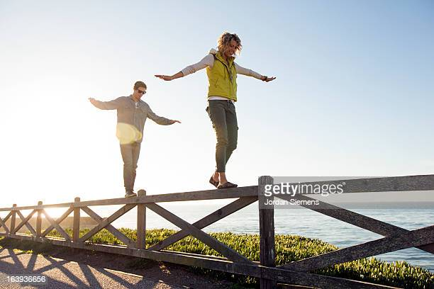 A couple balancing on a fence.
