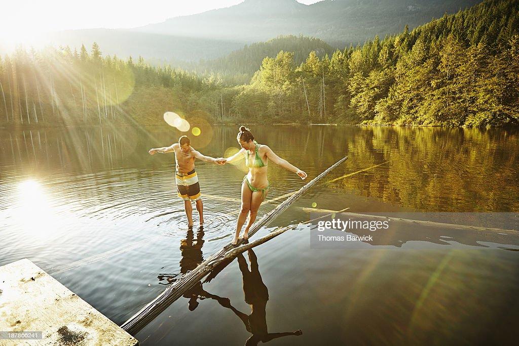 Couple balancing on logs in lake : Stock Photo