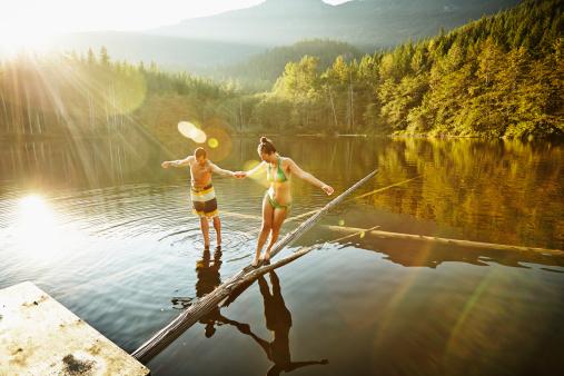 Couple balancing on logs in lake
