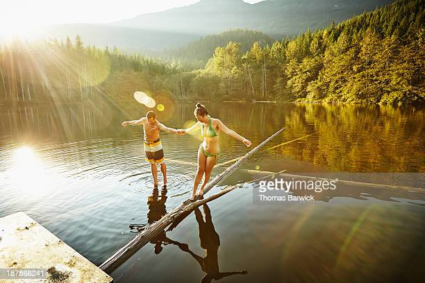 Couple balancing on logs in lake