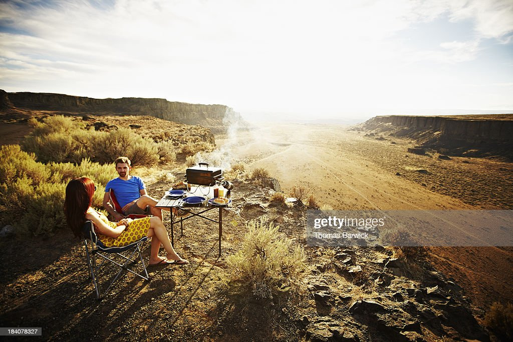 Couple barbecuing overlooking desert at sunset : Stock Photo