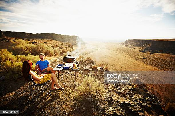 Couple barbecuing overlooking desert at sunset