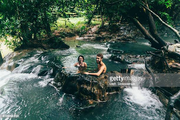 Couple bathing in hot spring waterfall