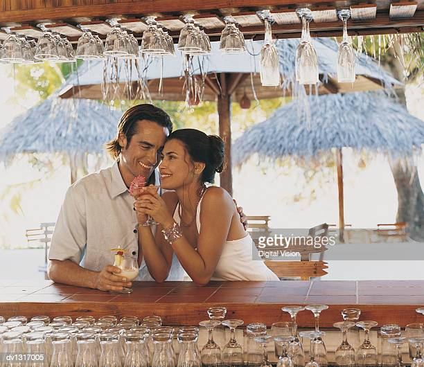 Couple Behind a Bar on a Beach Holding Cocktails