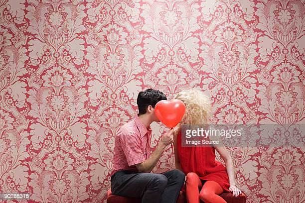 Casal atrás de balão em forma de coração