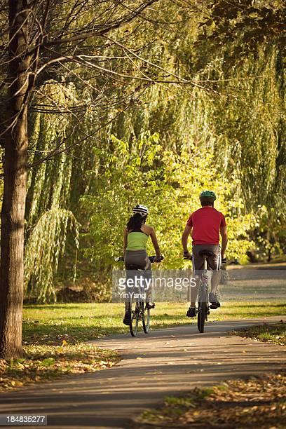 Radfahrern paar Radfahren im Herbst Park Radweg für die Übung