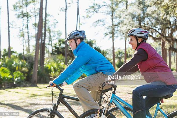 Couple biking in the park on chilly autumn day
