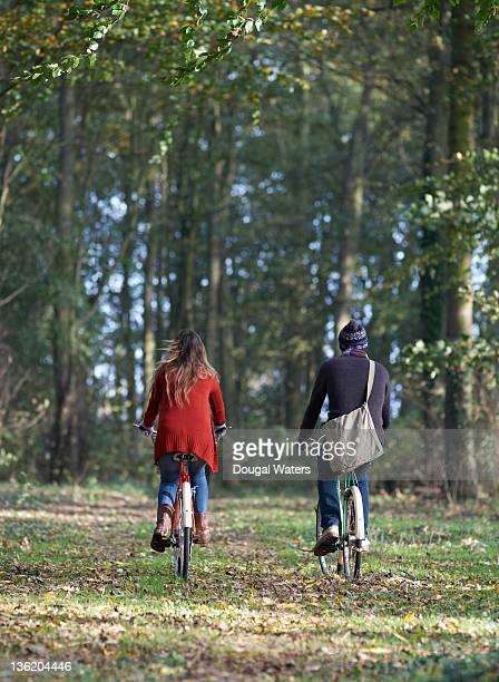 Couple biking together through woodland.