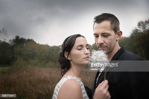 Couple blowing a dandelion