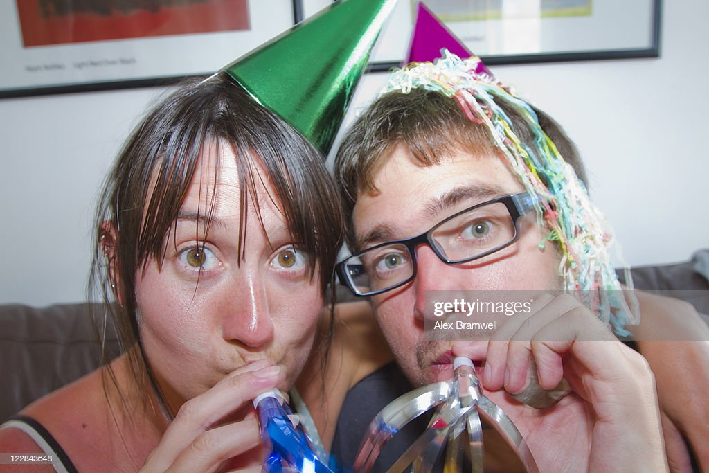 Couple blowing party horn blower