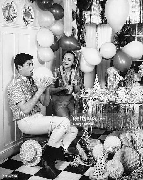 Couple blowing up balloons in kitchen for party, (B&W)