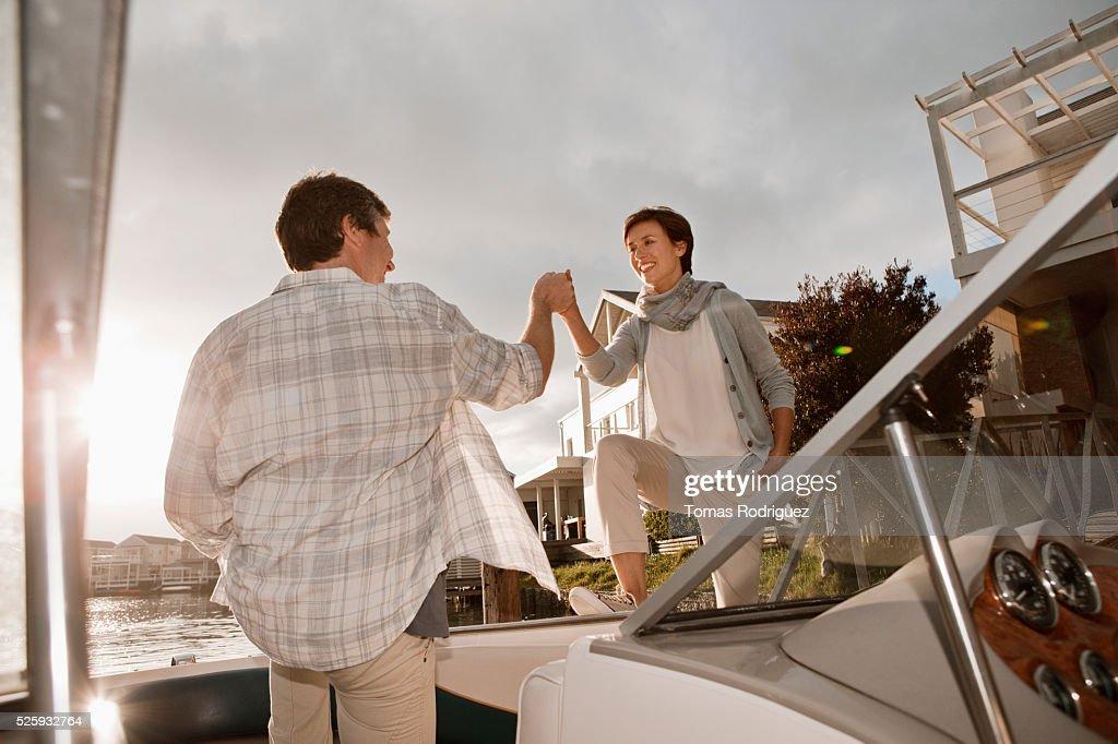 Couple boarding motorboat : Stockfoto