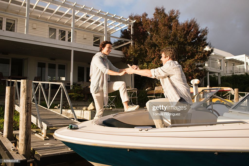 Couple boarding motorboat : Stockfoto