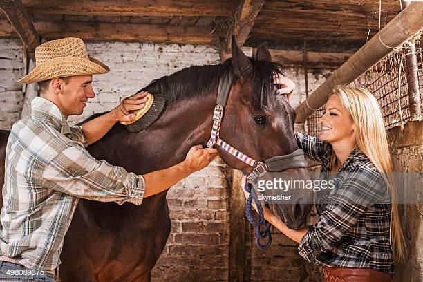 Couple brushing a horse.