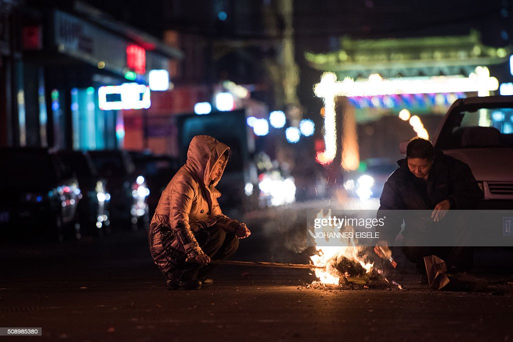 A couple burn incense along a street during Lunar New Year celebrations at the Chinese border town of Dandong, opposite to the North Korean town of Sinuiju, early on February 8, 2016, a day after North Korea said it had successfully put a satellite into orbit. The UN Security Council strongly condemned North Korea's rocket launch on February 7 and agreed to move quickly to impose new sanctions that will punish Pyongyang for 'these dangerous and serious violations.' With backing from China, Pyongyang's ally, the council again called for 'significant measures' during an emergency meeting held after North Korea said it had put a satellite into orbit with a rocket launch. AFP PHOTO / JOHANNES EISELE / AFP / JOHANNES EISELE