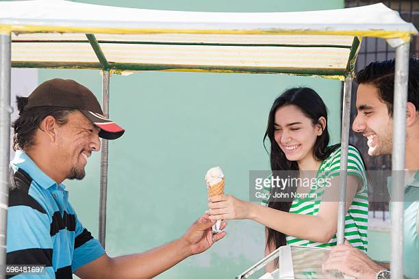 Couple buy an ice-cream from street vendor.