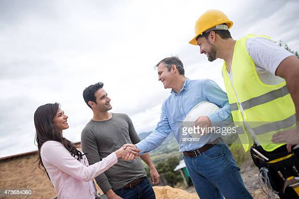 Couple buying a house and handshaking with the architect