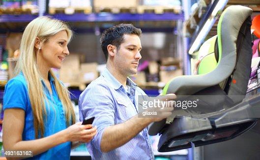 Couple buying baby car seat.