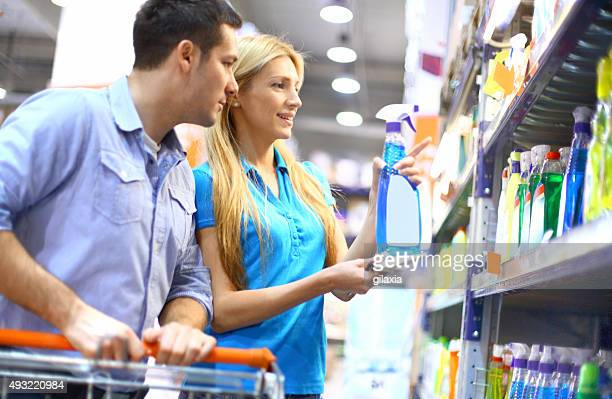 Couple buying cleaning liquid in supermarket.