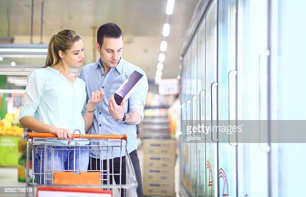 Casal comprar alimentos congelados no supermercado.