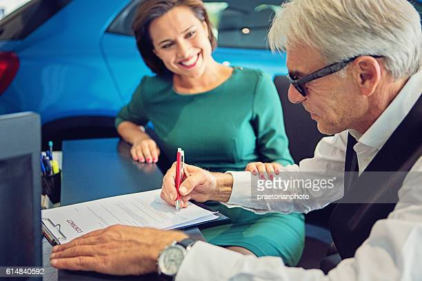 Couple buying new car and signing the contract