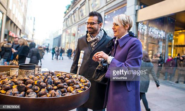 Couple buying roasted chestnuts on Milan street