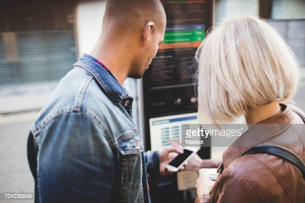 Couple buying tickets from vending machine at bicycle sharing system
