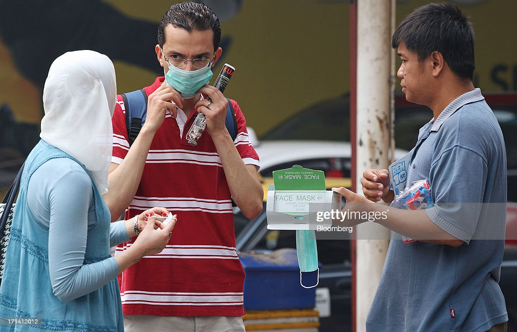 A couple buys face masks from a vendor on the street in Kuala Lumpur, Malaysia, on Monday, June 24, 2013. Malaysia called for a meeting of Southeast Asian ministers as early as next week after haze from illegal Indonesian forest fires reached hazardous levels in parts of the region. Photographer: Goh Seng Chong/Bloomberg via Getty Images