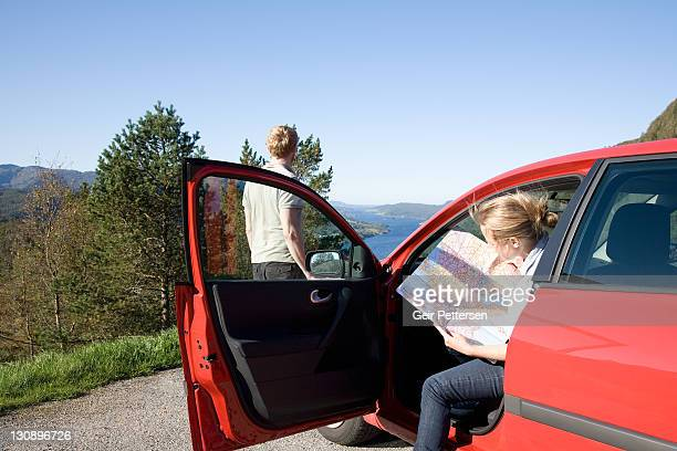 Couple by car studying map