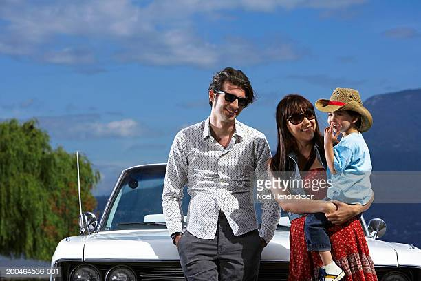 Couple by convertible car, woman holding son (2-4), smiling