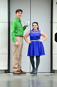 A couple stands by an elevator door wearing a blue dress and a green shirt while holding an ampersand sign.