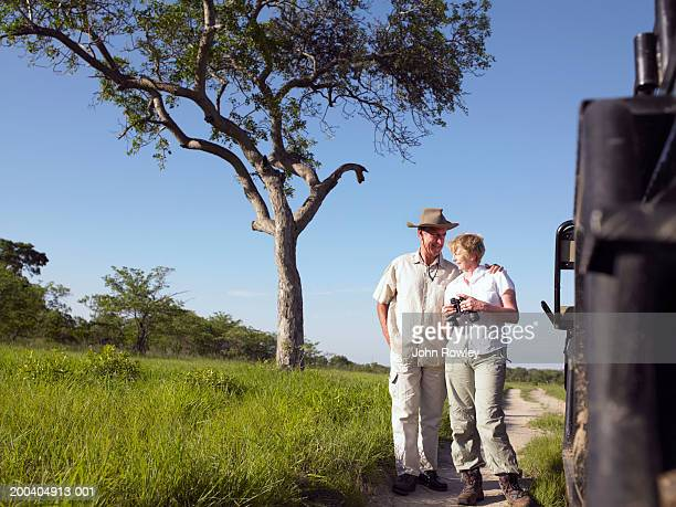 Couple en jeep, femme tenant jumelles, homme femme de passer le bras autour
