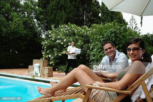 Couple by pool, smiling, portrait, man carrying towels in background