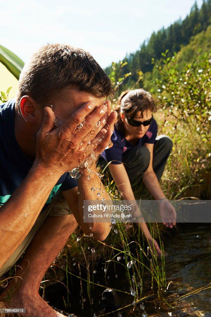 Couple by stream, man washing face, Chamonix, Haute Savoie, France : Stock Photo